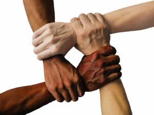 four community hands interlocked